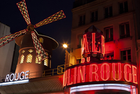 Low angle view of Moulin Rouge against residential building in city at night