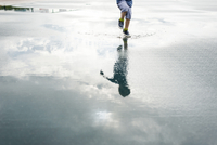 Reflection of boy jumping in puddle 11100048713| 写真素材・ストックフォト・画像・イラスト素材|アマナイメージズ