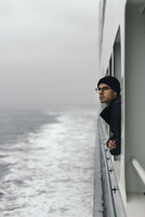 Thoughtful man looking through window while traveling in cruise ship