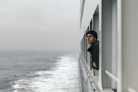 Man looking through window while traveling in cruise ship