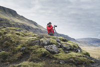 Man photographing while standing on hill against cloudy sky