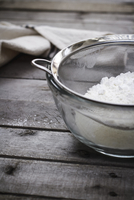 Close-up of flour in sieve over bowl on wooden table