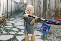 Portrait of boy holding baseball bat while standing in backyard 11100048814| 写真素材・ストックフォト・画像・イラスト素材|アマナイメージズ