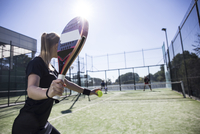 Woman playing tennis with friends in court on sunny day