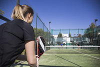 Woman looking at friends playing tennis in court against clear blue sky