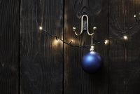 Christmas lights and bauble hanging on wooden wall