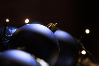 Close-up of Christmas baubles with fairy lights in dark room