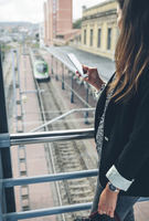 Side view of woman using phone while standing on footbridge over railroad track