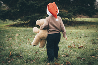 Rear view of boy in Santa hat holding teddy bear while walking on field 11100049261| 写真素材・ストックフォト・画像・イラスト素材|アマナイメージズ