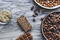 High angle view of chocolates bars with coco beans on kitchen counter