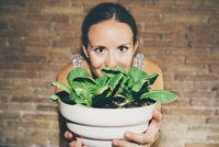 Portrait of woman holding houseplant while standing against brick wall