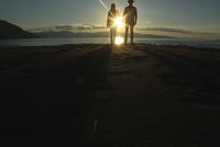 Silhouette couple standing on sand by lake during sunset