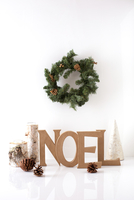 Text and decor on table with wreath hanging against white background