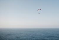 Person paragliding over sea