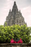 Rear view of women standing at Prambanan temple against clear sky 11100049601| 写真素材・ストックフォト・画像・イラスト素材|アマナイメージズ
