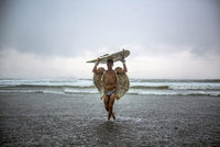 Man wearing angel wings carrying surfboard while walking in sea against cloudy sky 11100049629| 写真素材・ストックフォト・画像・イラスト素材|アマナイメージズ