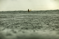 Distant view of woman surfing in sea during rainy season