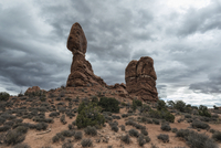 Low angle view of rock formations on field against cloudscape