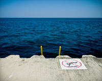 No swimming sign on pier over sea against clear blue sky