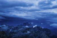 Scenic view of mountains against cloudy sky at dusk
