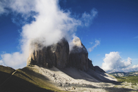 Scenic view of clouds over rock formation against blue sky