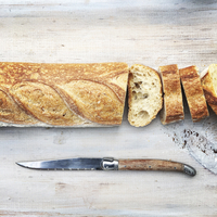 Sliced loaf of bread with knife on wooden table