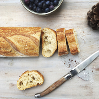 Overhead view of bread with knife by blueberries and pine cone on table