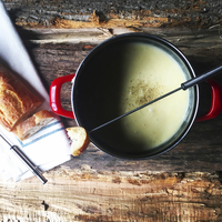 Overhead view of bread with cheese fondue on wooden table
