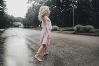 Girl standing on road by trees during rainy season 11100050447| 写真素材・ストックフォト・画像・イラスト素材|アマナイメージズ