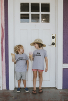 Happy siblings with ice cream looking at each other while standing against door
