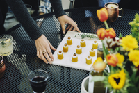 High angle view of woman placing appetizer on table in backyard 11100050640  写真素材・ストックフォト・画像・イラスト素材 アマナイメージズ
