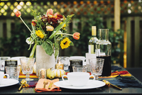 Flower vase with place setting and wine bottles on dining table in backyard