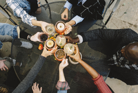 High angle view of friends toasting drinks while sitting at table in backyard