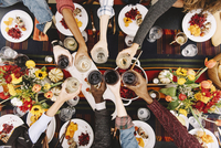 Overhead view of friends toasting drinks at table
