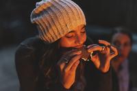 Woman enjoying smore while sitting in backyard at night 11100050710| 写真素材・ストックフォト・画像・イラスト素材|アマナイメージズ