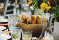 Breads in wooden bowl with drinks served on table