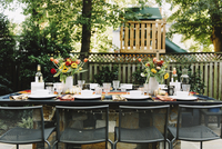 Place setting with empty chairs in backyard