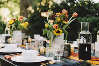 Flower vases with drinks and crockery arranged on table in backyard