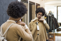 Woman selecting jacket while looking at mirror in shop