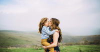Loving woman kissing daughter while standing on field against sky 11100050905| 写真素材・ストックフォト・画像・イラスト素材|アマナイメージズ