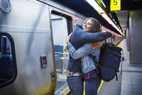 Loving couple embracing while standing at subway station by train