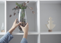 Cropped image of woman putting vase with Christmas decoration in shelf