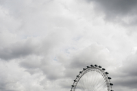 Low angle view of millennium wheel against cloudy sky