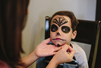Mother applying make-up on son's face at home