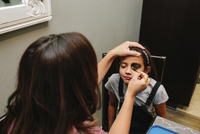 Woman applying make-up on daughter's face at home