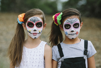 Portrait of sisters with face paint during Halloween
