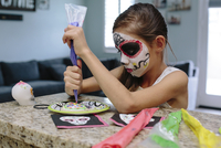 Girl with face paint decorating plate while sitting at table
