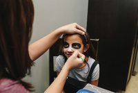 Woman applying make-up on smiling daughter's face at home