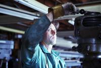 Worker adjusting machinery in workshop