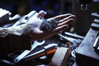 Cropped image of worker holding swarf in workshop